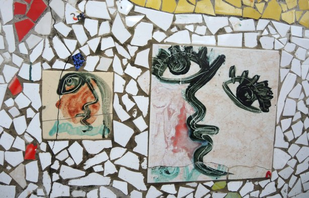 face made of bits of tile with some parts painted, part of a larger mosaic art piece, eyes looking slightly upwards and to the left