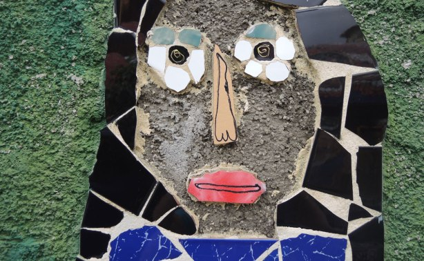 face made of bits of tile with some parts painted, part of a larger mosaic art piece, grey stucco face, shiny black tile hair and flower shaped eyes