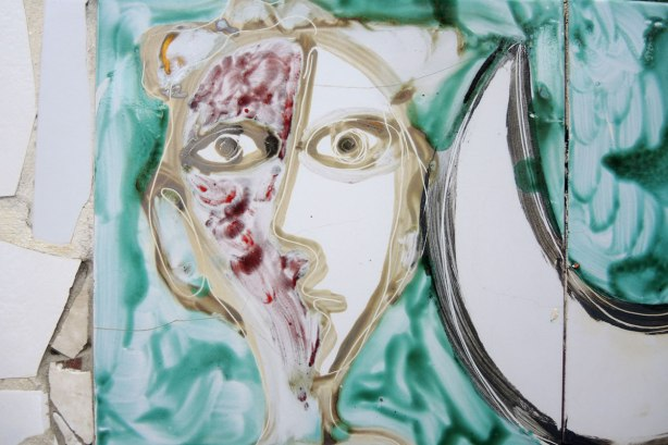 face made of bits of tile with some parts painted, part of a larger mosaic art piece, painted face on weird green background, a moon shape to the right of the face
