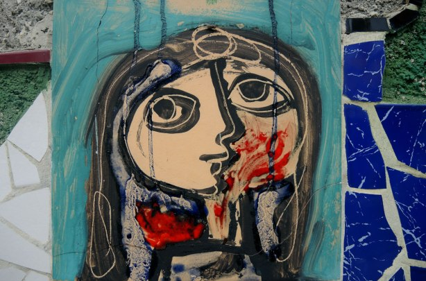 face made of bits of tile with some parts painted, part of a larger mosaic art piece, a young woman with long dark hair