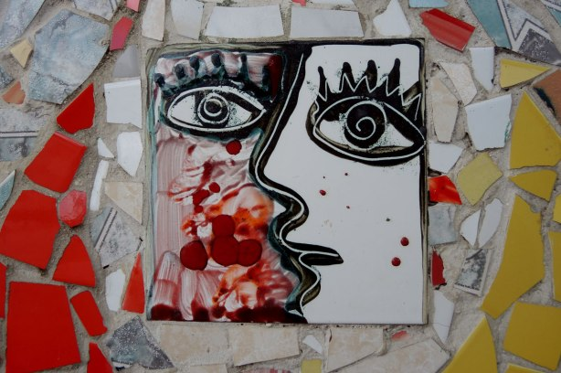 face made of bits of tile with some parts painted, part of a larger mosaic art piece, half red and half white face, black outline features