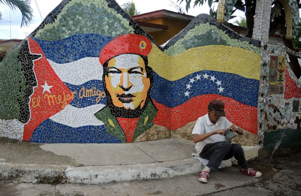 flags, cuban and bolivian, made of mosaics, with a man's head between the flags, wearing a red beret, a man is sitting on the sidewalk in front of the mosaic mural