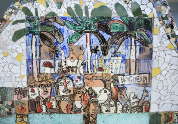 'no guerra' mural with many people and palm trees