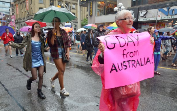 pride week, dyke march, a grey haired woman is carrying a pink sign that says 'G'day from Australia' and behind her is a couple of young women sharing a gren umbrella
