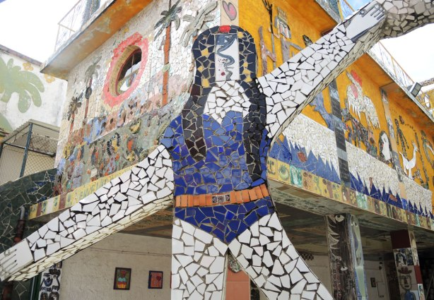 mosaic covered flat statue of a woman with long black hair, white arms and legs and wearing what looks like a blue one piece bathing suit