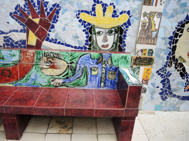 a brown bench with painted tiles behind it and on the back and arms of the bench such that it looks like a person wearing a yellow hat is sitting on the bench, although the person is flat, their arm is on the armrest of the bench.