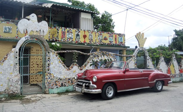 a Cuban house behind a wall that is covered with tile mosaic.  An old red car is parked in front of the building.