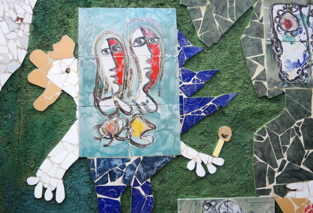 a mosaic chicken in blue and white with a painted tile (or two abstract female forms) in the center of it.