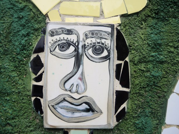 face made of bits of tile with some parts painted, part of a larger mosaic art piece, face in black and white on green stucco background