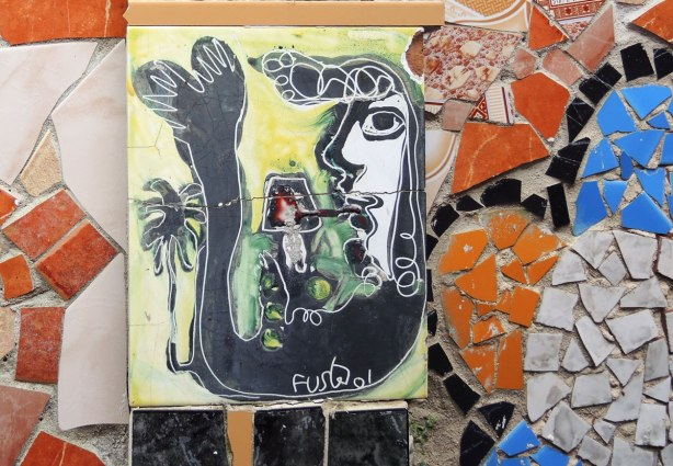 face made of bits of tile with some parts painted, part of a larger mosaic art piece