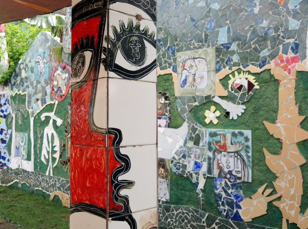 face made of bits of tile with some parts painted, part of a larger mosaic art piece, a red face and a white face in profile such that it also looks like one face, on a column with more mosaic on a wall behind