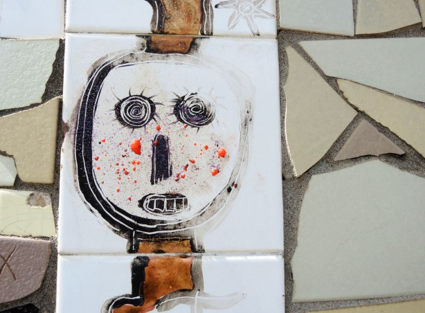 face made of bits of tile with some parts painted, part of a larger mosaic art piece, black on white face with lots of orange paint dots on the cheeks