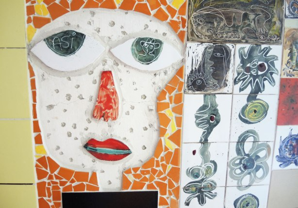 face made of bits of tile with some parts painted, part of a larger mosaic art piece, white face, black eyes, red nose