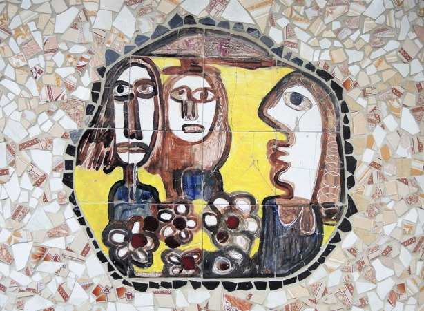 face made of bits of tile with some parts painted, part of a larger mosaic art piece, group of three faces and heads with some flowers in the middle and surrounded by a black circle