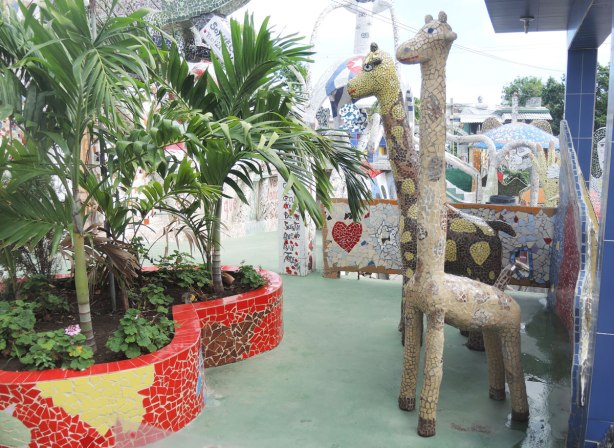 tile covered giraffe statues, 2, standing beside a large red heart shaped planter with small palm trees in it.