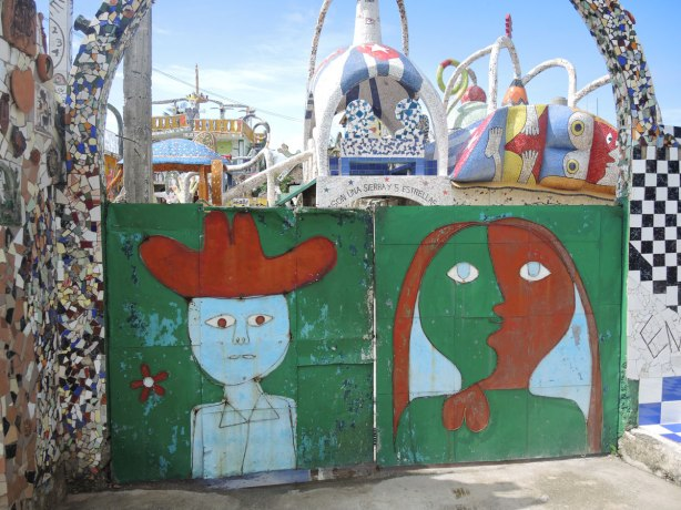 gate structure with two large faces on it, a man with red cowboy hat on the left and a person with half green and half red face on the right.