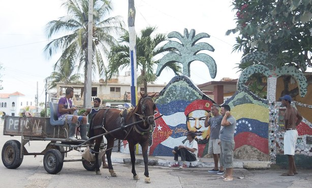 A horse drawn wagon and some men standing around on a corner.  A mural made of ceramic tiles is behind them including a life size cut out of a palm tree