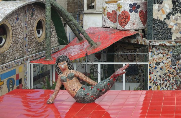 mosaic covered statue reclining on a red tile roof, she is surrounded by other mosaics and statues in the background.