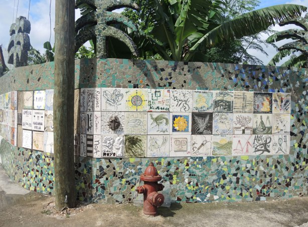 An exterior wall, or fence, covered with square tiles.  Some of the tiles have pictures on them and some of them have words on them.  There is a fire hydrant in front of the wall.