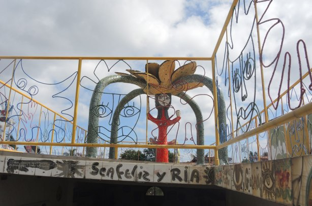 The words 'sea feliz y ria' painted on tiles around the bottom of a balcony.  A tile covered statue of a red person with a large flower on their head is also in the picture.   The balcony is surround by a wire fence, with faces made of metal open work in the railing too.