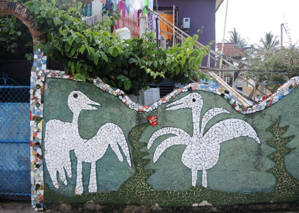 Two large white birds madde of tiles on a green background, a wall fence around a house.