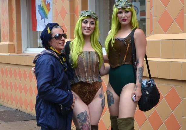 A woman in a blue jacket poses beside two scantily clad women with light lime green hair