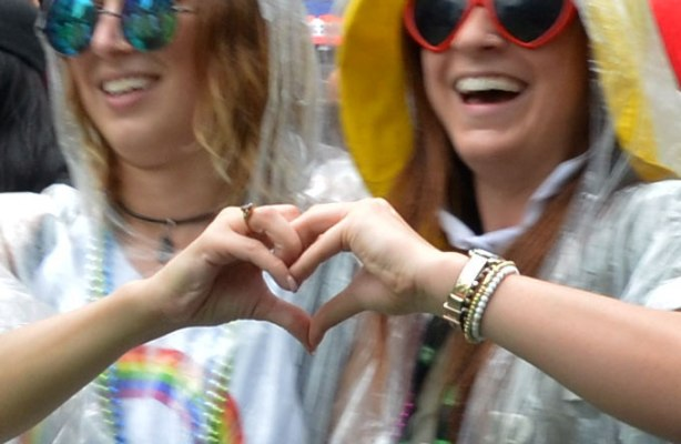#lovewins  Two young women in sunglasses walking in the pride parade join hands and make a heart shape with their fingers