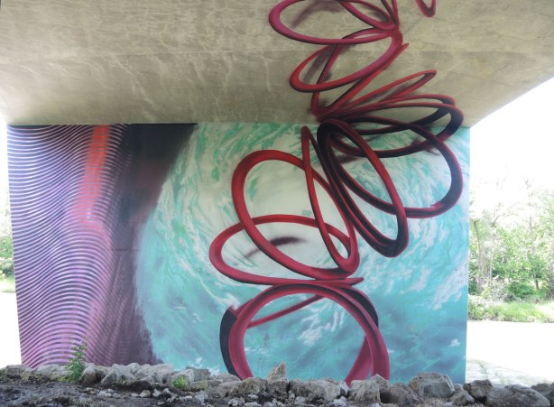 Mural of swirling water and a tangled spiral shape in red representing a hurrican rising from the eye of the storm upwards to the underside of the road
