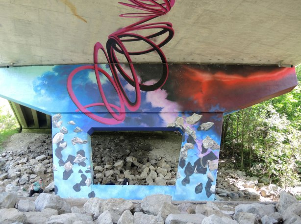 Mural on a concrete support of a bridge over a trail.  rocks on blue, with a tangled spiral shape in red representing a hurricane rising from the rocks (or ending at the rocks) and passing upwards to the under side of the road above.