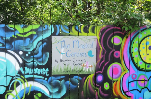 sign on a painted fence in a park that says 'The Magical Garden by Broadview Community Youth Group'