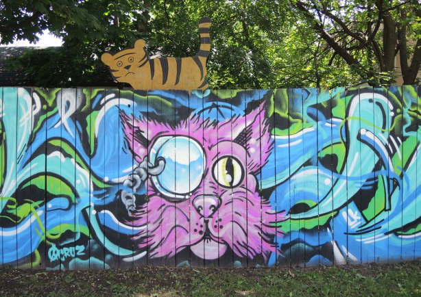Street art painting of a pink cat head on a fence with a cutout brown and black cat above it.
