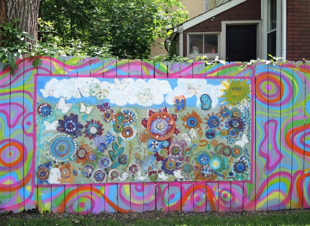 On a fence in a park - a mural, or collage, abstract flowers made of circles and squares in many bright colours.