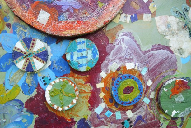 Close up of part of a mural, or collage, abstract flowers made of circles and squares in many bright colours.