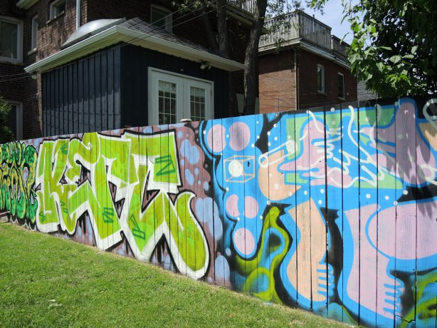 park fence with house behind, fence is painted with street art