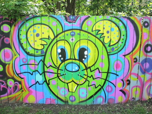 street art painting of a bright green and yellow mouse head