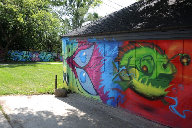 in the foreground is a garage with two pieces of street art, a little green monster on a red background, and half a butterfly