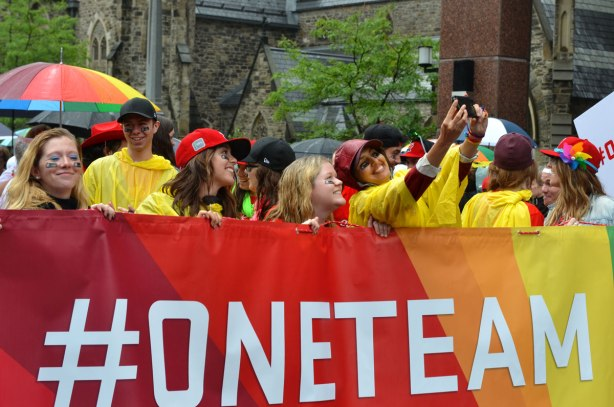 A group of people holding a large rainbow coloured banner that says #oneteam.  Some of them are taking selfies