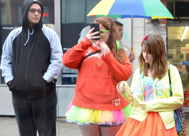 Three people on a sidewalk.  A man in a black and grey hoodie who is looking at the two women beside him.  One woman is in a multicoloured tutu and an orange sweatshirt.   She is looking at her phone.  The other woman is wearing an ornage skirt and a yellow sweater