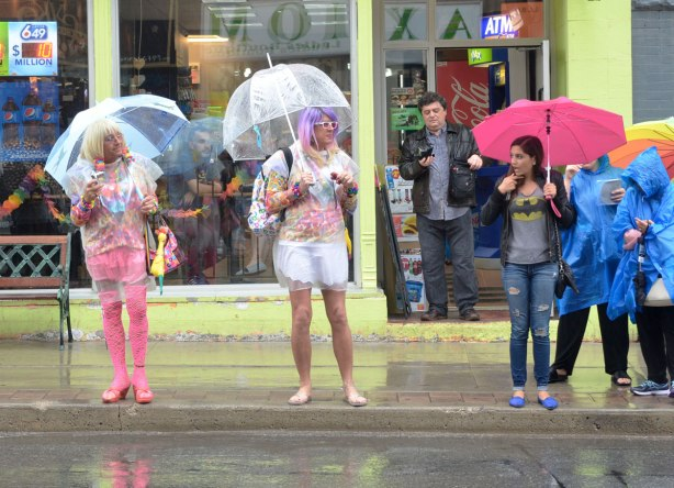 Two men in colourful and glamorous drag are standing on a sidewalk in the rain.  They are each holding a clear umbrella.  A girl is standing beside them with an astonished look on her face.