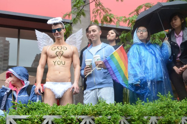people at a pride parade on a rainy day - a few people have found a higher vantage point from which to watch the parade.  One man is wearing white frilly underpants and white angel wings.  On his stomach is written God 'heart' you