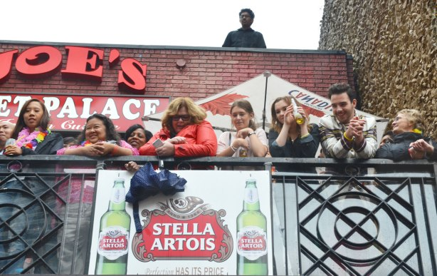 people at a pride parade on a rainy day - a group watches the parade from the balcony of a bar