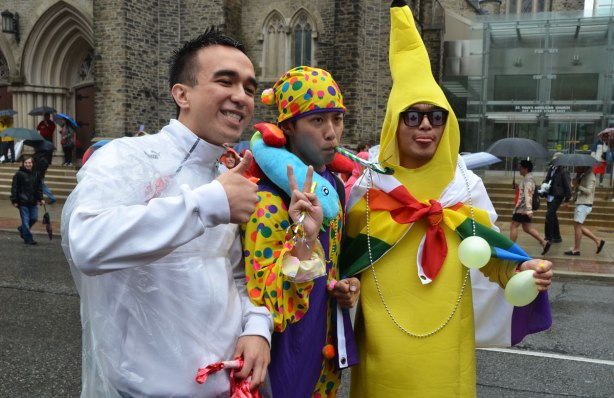 people at a pride parade in the rain - three guys posing for a photo, one is in a banana costume
