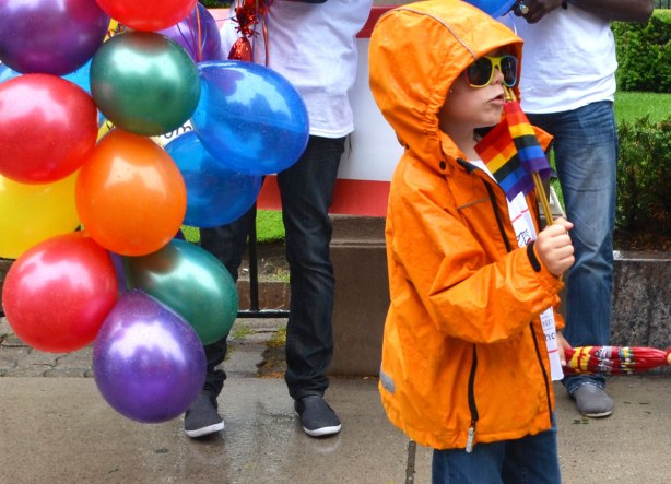people at a pride parade in the rain - boy in ornage raincoat and sunglasses standing in front of many balloons