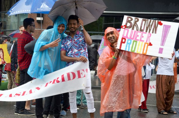 "people at a pride parade in the rain - three Asain guys, two under an umbrella, and a third wearing a salmon coloured rain poncho and holding up a sign that says ""brown queer proud'"