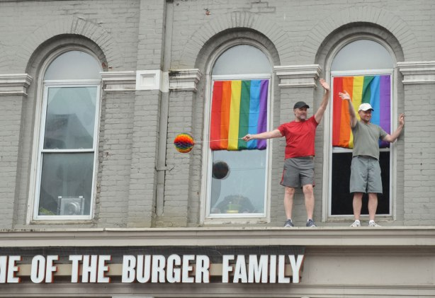Two men stand on an exterior ledge of a building, one storey up from ground level.  Two rainbow flags too.