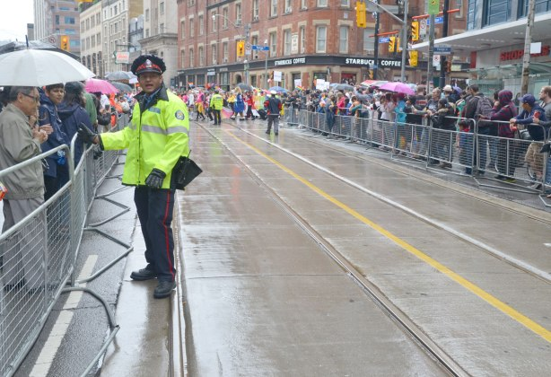 people at a pride parade on a rainy day - a policeman helps with crowd control along the barricades of the parade route