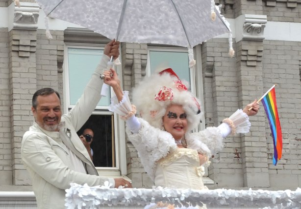 people at a pride parade on a rainy day - Cyndi Lauper is wearing a white frilly dress and hat as she rides on top of a float for the musical KInky Boots.  In the background a photographer leans out the window of a building to get a better view of the parade.