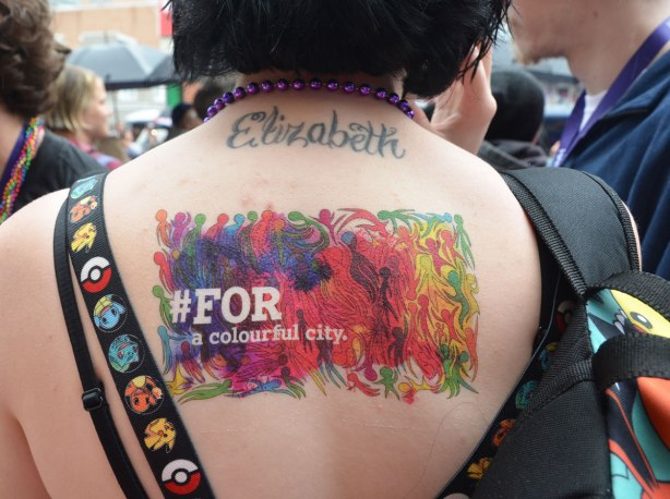 people at a pride parade on a rainy day - the back of a woman with short black hair.  She has a tattoo across the back of her neck that says Elizabth as well as a temporary colourful tattoo that includes the words #for a colourful city