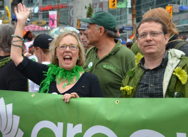 Elizabeth May, wearing a green garland wrapped around her neck and helping to hold a green banner walks in a parade along with some other people