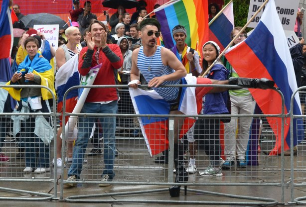 people at a pride parade on a rainy day - one of the parade marchers, while holding a French flag, stops to lift his leg over the barricades